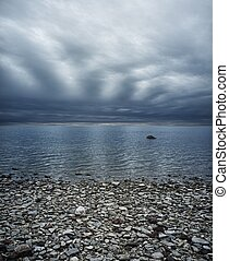 Moody sky over rocky beach