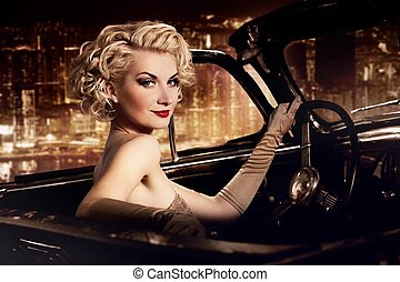 Woman in retro car against night city.