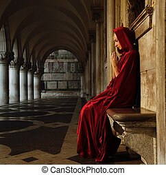 Woman in red cloak praying alone
