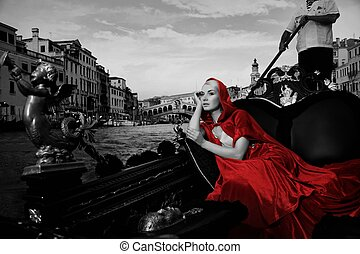 Beautiful woman in red cloak riding on gondola