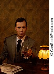 Businessman sitting behind table with a drink