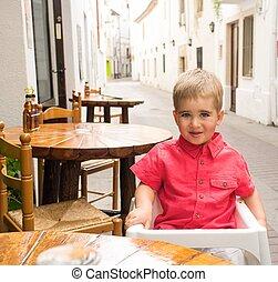 Little boy in steet cafe