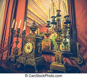 Antique clock and chandelier against mirror