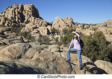 Taking in the Granite Dells - a female hiker pauses to take...