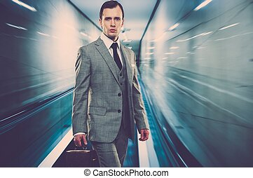 Man in classic grey suit with briefcase standing on...