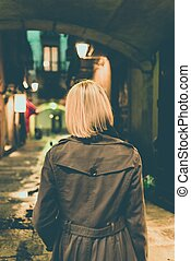 Blond woman in raincoat walking alone outdoors at night