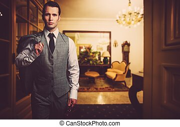 Man in grey waistcoat with briefcase in luxury home interior