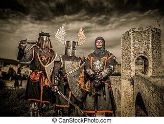 Three knight in armor against Romanesque bridge over river ,...