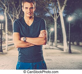 Young man in shirt outdoors at night