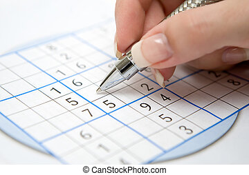 Sudoku - Female hand holding pen and doing a Sudoku game