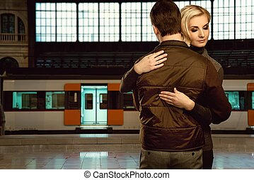 Beautiful couple embracing on train station