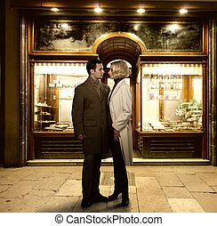 Elegant couple against bakery shop window