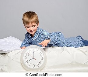 Little boy in blue pajamas with clock