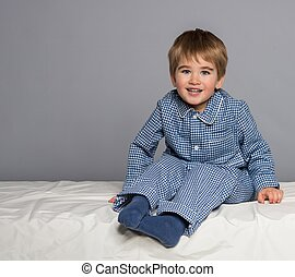 Playful little boy wearing blue pyjamas in bed