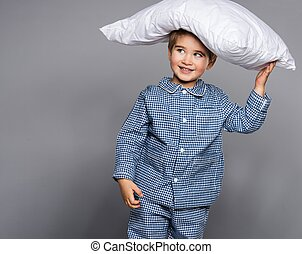 Little boy in blue pajamas with pillow