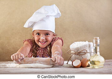 Happy little chef stretching the dough