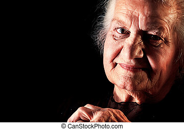 old age - Portrait of a happy senior woman smiling at the...