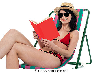 Enticing bikini model on a deckchair reading a book -...