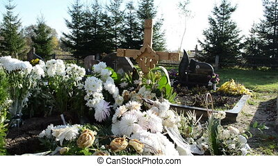 new grave flowes cross - new grave in cemetery graveyard...