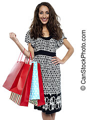 Shopaholic brunette carrying vibrant color bags isolated...