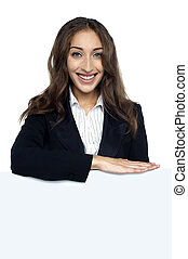 Female executive behind blank white ad board, business...