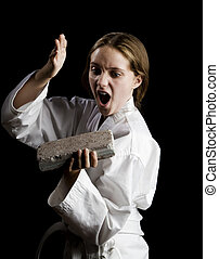 Young girl karate chopping a brick on black background