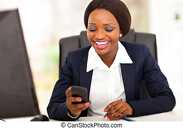 happy african american busniesswoman reading sms in office