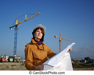 Young architect looking at blueprint in front of...