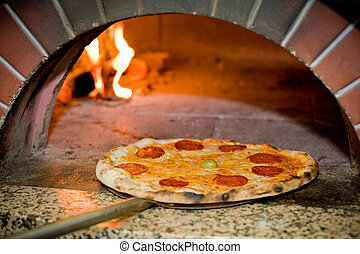 Delicious baked pizza in front of oven