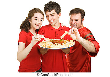 Partiers Snacking - Handsome teen boy serves chips at a...