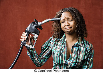 Woman Holding Gas Nozzle to her Head - Woman holding gas...