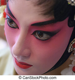 a chinese opera actress is painting her face before the...