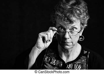 Woman looking over her glasses - Senior woman looking over...