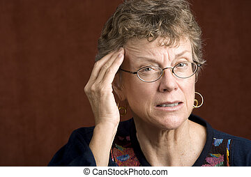 Woman with a headache - Senior woman with a headache rubbing...