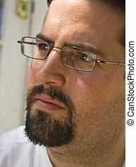 Man with beard and glasses looks left intently