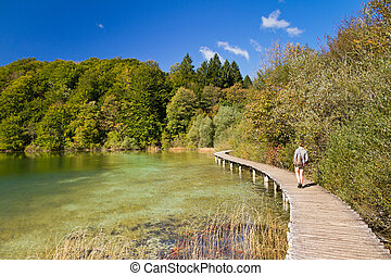 Plitvice lake path - Woman walking on the wooden footpath...