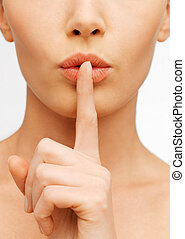 woman making a hush gesture - closeup picture of woman...