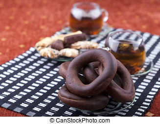 plate with pretzel next to a cup of tea