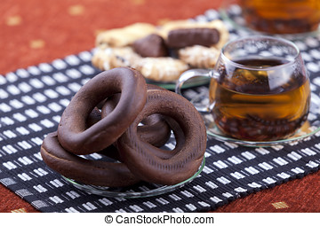 plate with pretzel next to two cups of tea