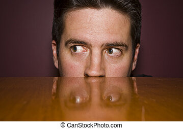 Sneaky peek over a table - A man peeks over a table