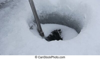 chipping an ice fishing hole - chipping out an ice fishing...