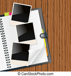 retro photo frames on open diary with wooden background