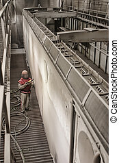 Sandblasting a train cart - A worker sandblasting a train...