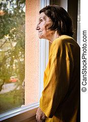 Solitude - senior woman looking through window - Solitude...