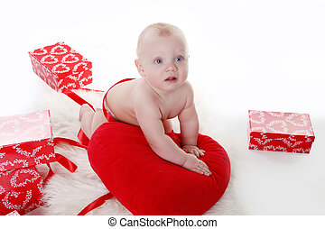 Lovely baby with Valentines heart and gifts boxes over white...