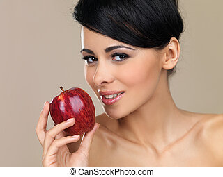 Beautiful brunette with a red apple - Beautiful young...