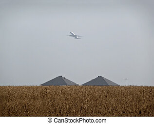 Airplane - Commercial jet airplane over wheat field against...