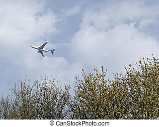 Airplane - Commercial jet airplane over yellow blooming tree...