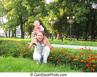 Happy mum and the daughter in park with flowers