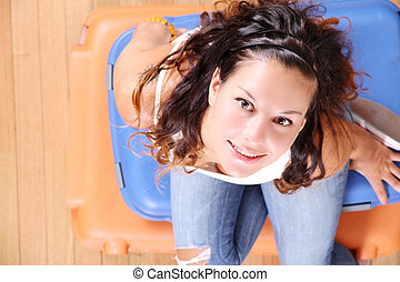 Girl sitting on suitcases - A young woman sitting on a stack...